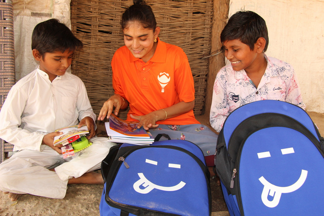 A Hope Carrier volunteer shows two boys lessons included in their school bags