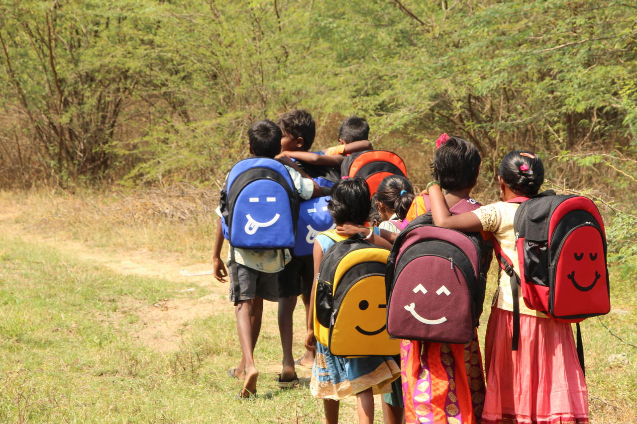 A small group of children walk home after receiving their backpacks