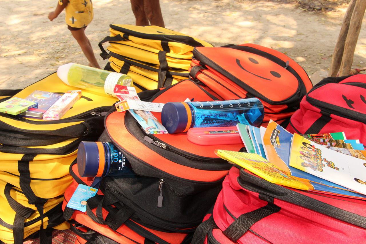 Our backpack in yellow, orange and red with a close-up of some of the essential inserts that go in each school bag