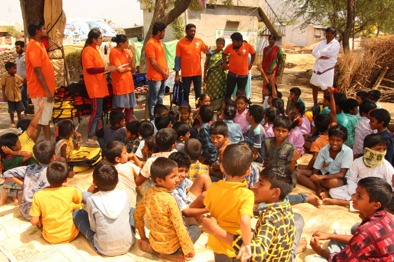 Children listening to the story of Jesus as they wait for their backpack