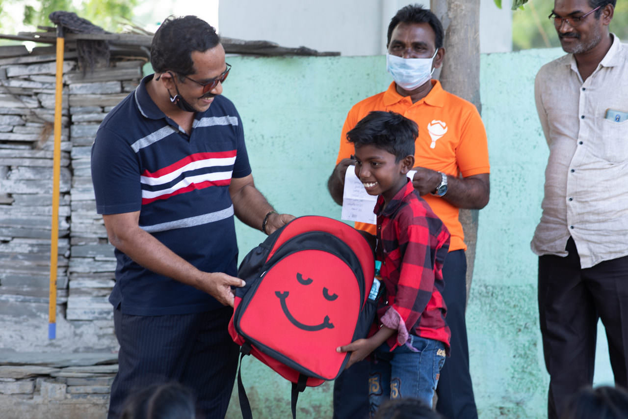 Eager boys and girls receive their school bag and essentials